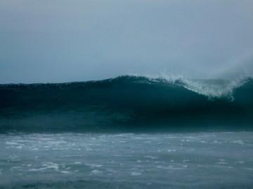 En un lado de la isla fuertes olas rompen a lo lejos en el arrecife