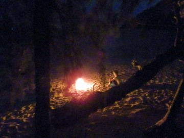 Valentine sitting in front of the bonfire at night