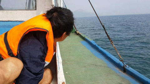 Ho Van Lang (the real life Tarzan) on the boat looking at the desert island at the distance