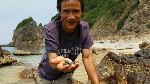 Ho Van Lang (the real life Tarzan) showing to the camera the shells he collected